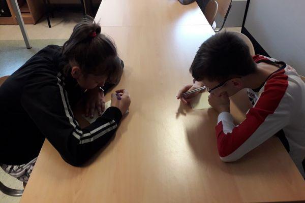 Zdjęcie przedstawia dwójkę siedzących przy stoliku dzieci chłopca i dziewczynkę piszących na kartce