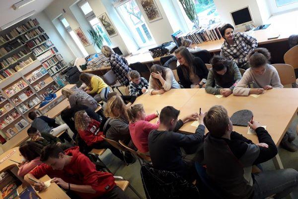 Zdjęcie przedstawia młodzież wraz z nauczycielami siedzącą przy stołach, piszącą na kartkach