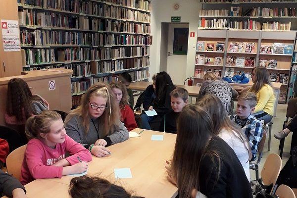 Zdjęcie przedstawia młodzież siedzącą wraz z nauczycielami przy stołach w czytelni WCK