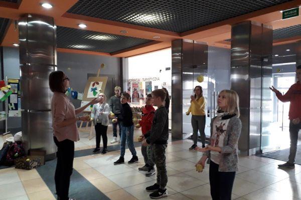 Zdjęcie przedstawia po lewej stronie prowadzącą warsztaty żonglowania, po prawej stronie uczestników warsztatów