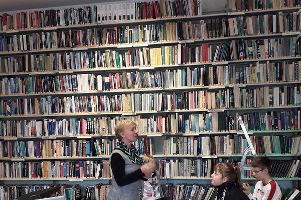 Zdjęcie przedstawia pomysłodawczynię projektu stojącą na tle ściany z półkami pełnymi książek