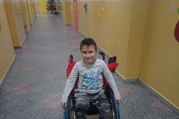 Zdjęcie przedstawia Adriana, chłopca niepełnosprawnego ruchowo na szkolnym korytarzu. Chłopiec siedzi na swoim nowym wózku inwalidzkim.