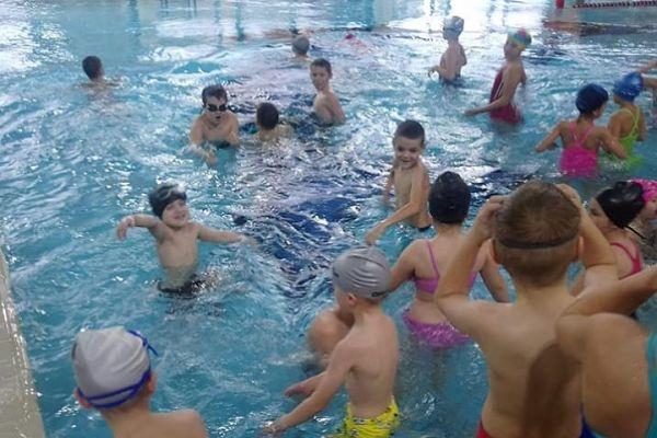 Zdjęcie przedstawia uczniów klasy 1b w czasie zabawy w wodzie na basenie.