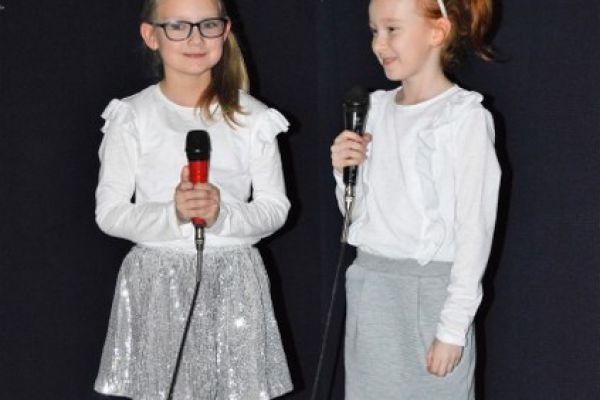 Zdjęcie przedstawia dwie uczennice klasy pierwszej. Dziewczynki stoją po środku sceny. W tle widać gwieździste niebo