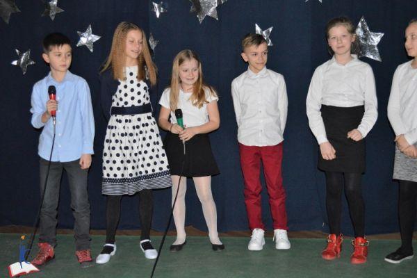 Zdjęcie przedstawia uczniów klasy 4 - dwóch chłopców i cztery dziewczynki. Uczniowie stoją na tle zimowej, gwieździstej dekoracji